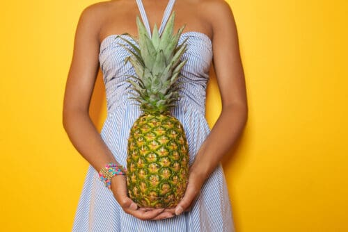 Beautiful African-American woman with pineapple on color background