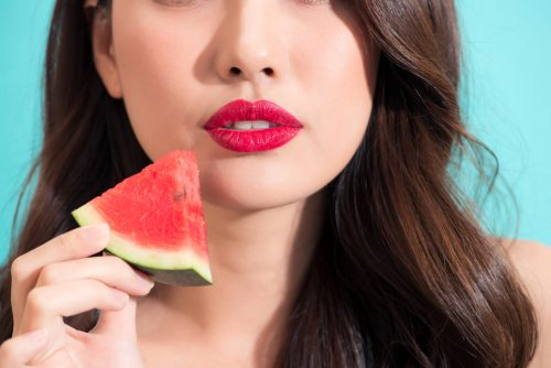 Close-up of a beautiful women holding watermelon slice with red lips.