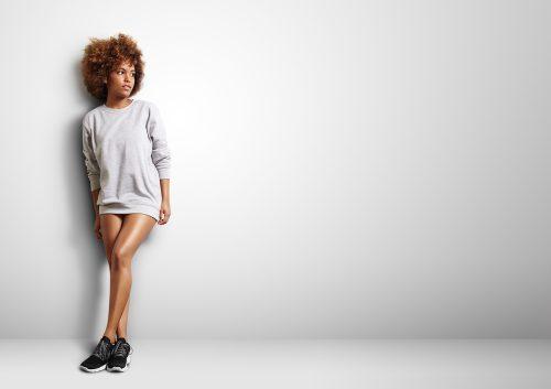 black woman wearing a sweatshirt like a dress