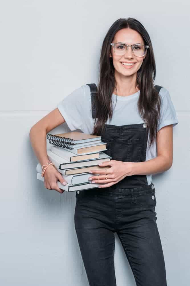 young caucasian woman holding books and looking at camera