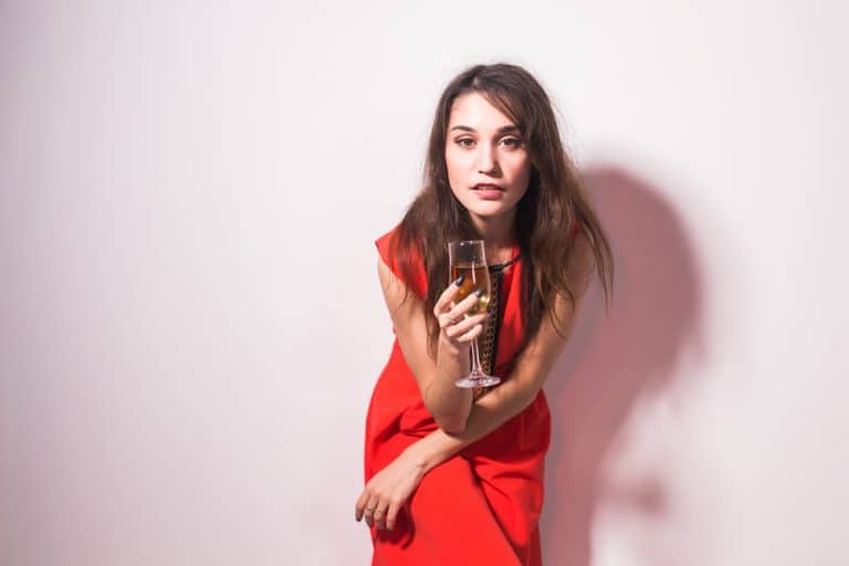 Party, holidays and celebrations concept - Cheerful charming young woman in red dress drinking champagne or wine and dancing over white background